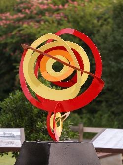 A red, yellow and orange mix of circles. Sculpture named Equator