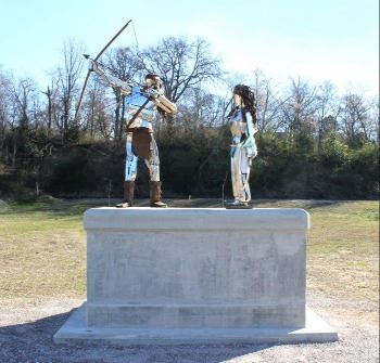 A large metal sculpture of an Native American Indian man shooting an arrow and his wife behind him w